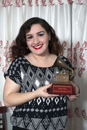BRONX, NEW YORK - DECEMBER 23: Yomo Toros niece Christina holds  Latin Grammy in honor of international cuatro player Yomo Toro who was awarded the Grammy but passed away before he could accept it. Taken December 23, 2012 in the Bronx, NY.