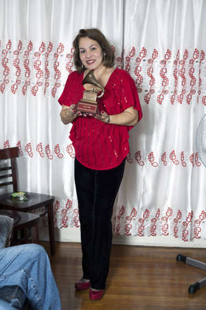 BRONX, NEW YORK - DECEMBER 23: Yomo Toros niece Elizabeth holds Latin Grammy in honor of international cuatro player Yomo Toro who was awarded the Grammy but passed away before he could accept it. Taken December 23, 2012 in the Bronx, NY. Editorial