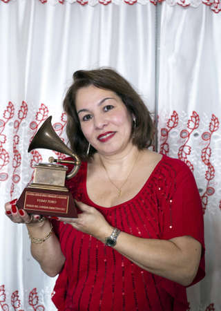 fania all stars: BRONX, NEW YORK - DECEMBER 23: Yomo Toros  Yomos niece Elizabeth  holds Latin Grammy in honor of international cuatro player Yomo Toro who was awarded the Grammy but passed away before he could accept it. Taken December 23, 2012 in the Bronx, NY. Editorial