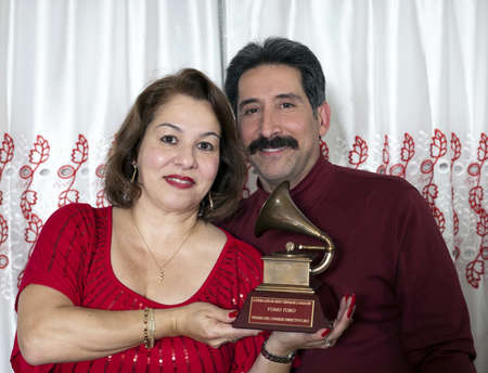 fania all stars: BRONX, NEW YORK - DECEMBER 23: Yomo Toros niece Elizabeth and her husband Andy hold  Latin Grammy in honor of international cuatro player Yomo Toro who was awarded the Grammy but passed away before he could accept it. Taken December 23, 2012 in the Bronx Editorial