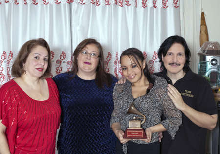 BRONX, NEW YORK - DECEMBER 23:  From left to right are Yomo Toro's niece Elizabeth, Yomo's wife Minerva, friend Katiria and nephew Eddie Toro with Latin Grammy  as they unite to remember international cuatro player Yomo Toro who was awarded the Grammy but Stock Photo - 17262519