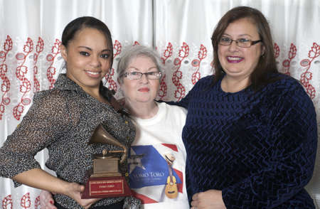 BRONX, NEW YORK - DECEMBER 23: Yomo Toros wife Minerva on right, his sister Lydia and Yomos adopted daughter of music Katiria  hold  Latin Grammy in honor of international cuatro player Yomo Toro who was awarded the Grammy but passed away before he coul