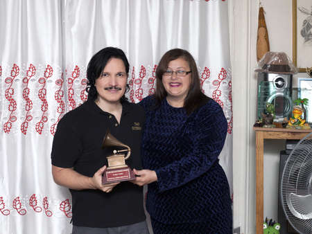 BRONX, NEW YORK - DECEMBER 23: Yomo's wife Minerva and nephew Eddie Toro remember international cuatro player Yomo Toro who was awarded the Latin Grammy but passed away before he could accept it. Taken December 23, 2012 in the Bronx, NY. Stock Photo - 17262508