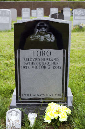 QUEENS, NEW YORK - JUNE 6: Grave of Yomo Toro, master of the Puerto Rican guitar like instrument called a cuatro.   Taken June 6, 2013 at Saint Michaels Cemetery in New York. Editorial