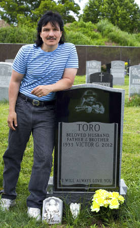 fania all stars: QUEENS, NEW YORK - JUNE 6:  nephew Eddie Toro visits grave of Yomo Toro, master of the Puerto Rican guitar like instrument called a cuatro on anniversary of his death.   Taken June 6, 2013 at Saint Michaels Cemetery in New York.