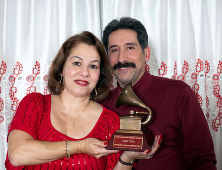 Yomo Toro s niece Elizabeth and husband Andy hold  Latin Grammy in honor of cuatro player Yomo Toro who passed away before he could accept it  Taken December 23, 2012  Bronx, NY  Editorial