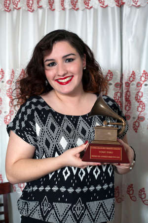 Yomo Toro s niece Christina holds  Latin Grammy in honor of international cuatro player Yomo Toro who  passed away before he could accept it  Taken December 23, 2012  Bronx, NY