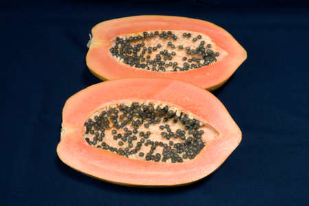 A papaya fruit cut in half and photographed against a black background.