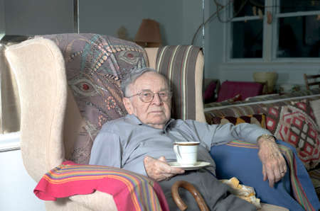 A senior man sits on his couch with cup of hot drink in his home.  He is of Jewish ethnicity. photo