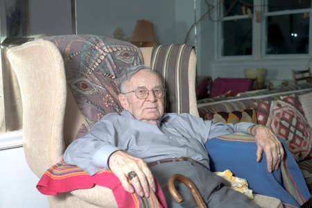 A senior man sits on his couch in his home.   photo