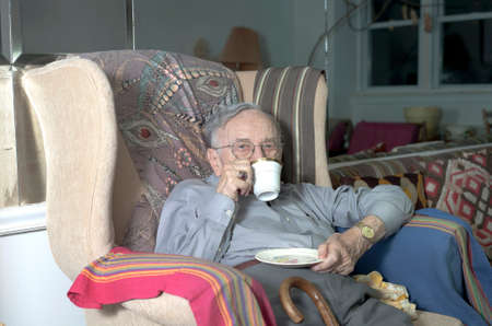 A senior man sits on his couch with cup of hot drink in his home.   photo