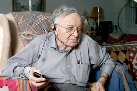 A senior man sits on his couch with his headphone device.   photo