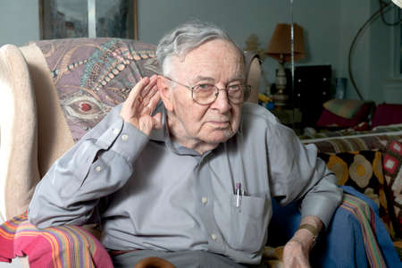 A senior man making a repeat or speak louder gesture with his hand. photo