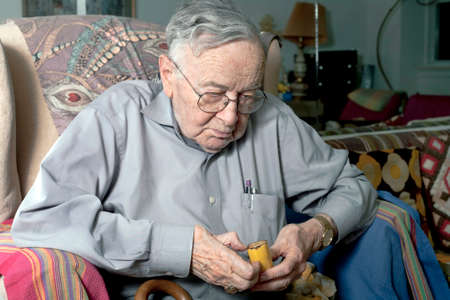 A senior man sits on his couch eating a banana. photo