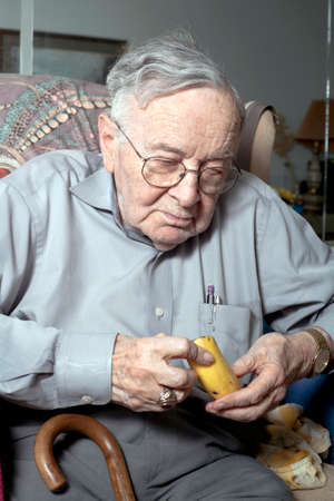 A senior man sits on his couch in his home with a banana.   photo