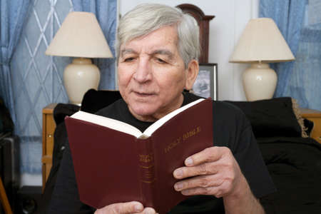 king james: A senior man reads the King James Bible.