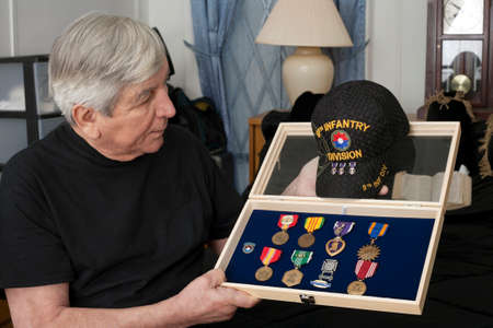 earned: BRONX, NEW YORK - MAY 26: Vietnam veteran Franky Gonzalez looks holds medals earned during service.  Taken May 26, 2013 in New York City. Editorial