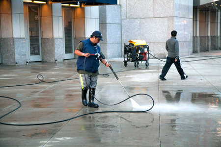 bronx county: BRONX, NEW YORK - MAY 29: Man uses pressure washer to clean Yankee Stadium sidewalk.   Taken May 29, 2014 in the County of the Bronx, NY. Editorial