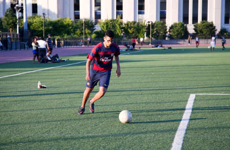 bronx county: BRONX, NEW YORK - JUNE 19: Young man playing soccer on the jogging field near Yankee Stadium.   Taken June 19, 2014 in the County of the Bronx, NY. Editorial