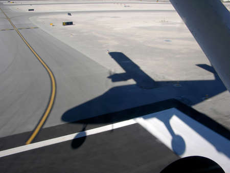 small plane: Shadow of small plane is cast on the runway as it lands. As viewed from inside plane. Stock Photo