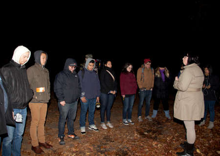 paranormal: HUNTINGTON, NEW YORK, USA - NOVEMBER 14,  2015: Lindsay Klinger leads members of the Brooklyn Paranormal Society of New York in meditation before their investigation of Mount Misery Road in Long Island. Known for tales and legends of paranormal sightings.