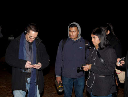 paranormal: HUNTINGTON, NEW YORK, USA - NOVEMBER 14,  2015: Ron Yacovetti checks his audio recording device as other members of the Brooklyn Paranormal Society of New York watch during their investigation of Mount Misery Road in Long Island. Known for tales and legen