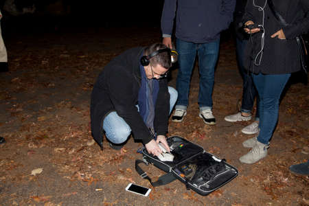 paranormal: HUNTINGTON, NEW YORK, USA - NOVEMBER 14,  2015: Ron Yacovetti checks his equipment as other members of the Brooklyn Paranormal Society of NY stand nearby during their investigation of Mount Misery Road in Long Island. Known for tales and legends of parano Editorial