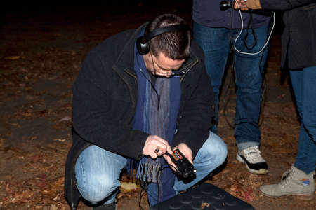 investigates: HUNTINGTON, NEW YORK, USA - NOVEMBER 14,  2015: Ron Yacovetti checks his audio recording device  as the Brooklyn Paranormal Society of NY investigates Mount Misery Road in Long Island. Known for tales and legends of paranormal sightings. Editorial
