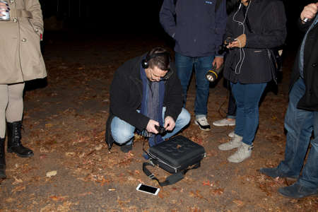 paranormal: HUNTINGTON, NEW YORK, USA - NOVEMBER 14,  2015: Ron Yacovetti checks his audio recording device  as other members of the Brooklyn Paranormal Society of NY stand nearby during their investigation of Mount Misery Road in Long Island. Known for tales and leg