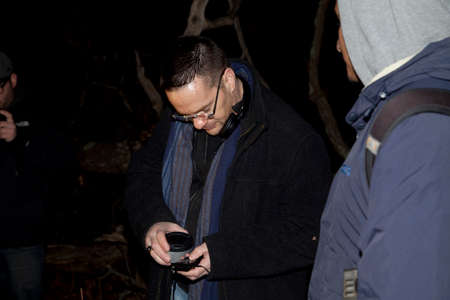 HUNTINGTON, NEW YORK, USA - NOVEMBER 14,  2015: Ron Yacovetti checks his recording device  as the Brooklyn Paranormal Society of NY investigates Mount Misery Road in Long Island. Known for tales and legends of paranormal sightings.