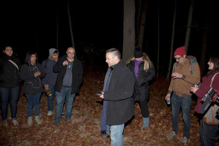 paranormal: HUNTINGTON, NEW YORK, USA - NOVEMBER 14,  2015: Members of the Brooklyn Paranormal Society of NY during their investigation of Mount Misery Road in Long Island. Known for tales and legends of paranormal sightings.  They are standing and taking readings on Editorial