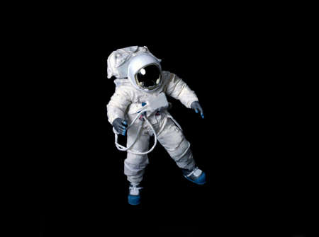 Astronaut wearing a pressure suit against a black background. Stock Photo