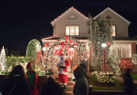 saint nick: BROOKLYN, NEW YORK, USA - DECEMBER 19: A house with Christmas lights and Santa Vincent Privitelli between 11th and 12th avenue and 83rd street. Donations raised for Alzheimers awareness. Taken December 19, 2015 in New York.