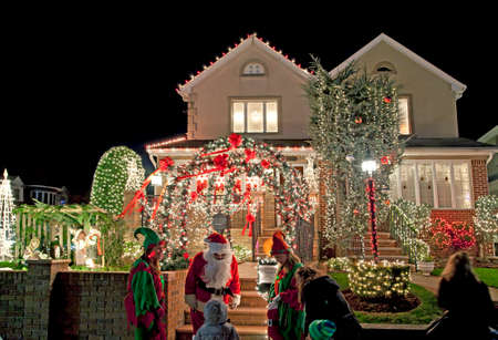 saint nick: BROOKLYN, NEW YORK, USA - DECEMBER 19: A child visits house with Christmas lights and Santa Vincent Privitelli between 11th and 12th avenue and 83rd street. House owned by Vincent with donations raised for Alzheimers awareness. Taken December 19, 2015  Editorial