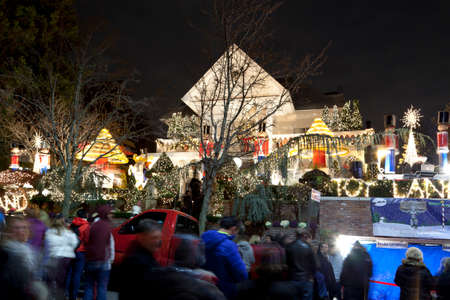 see the usa: BROOKLYN, NEW YORK, USA - DECEMBER 19: People gather to see a house with Christmas lights  between 11th and 12th avenue and 83rd street in Dyker Heights. Taken December 19, 2015 in New York. Editorial