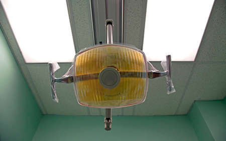 A standard Halogen dental light fixture hung from cieling.