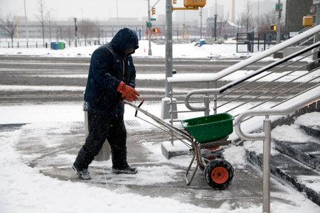 BRONX, NEW YORK, USA - FEBRUARY 19: Man uses salt spreader during snowfall.  Taken February 19, 2015 in the Bronx,  New York.