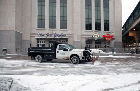 snow plow: BRONX, NEW YORK, USA - FEBRUARY 19: A truck with a plow clears snow in front of Yankee Stadium.  Taken February 19, 2015 in the Bronx,  New York.