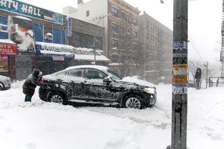 bronx county: BRONX, NEW YORK - JANUARY 23: Man pushes stuck auto on Anderson Avenue street during Blizzard storm Jonas.  Taken January 23, 2016, in the Bronx,  New York. Editorial