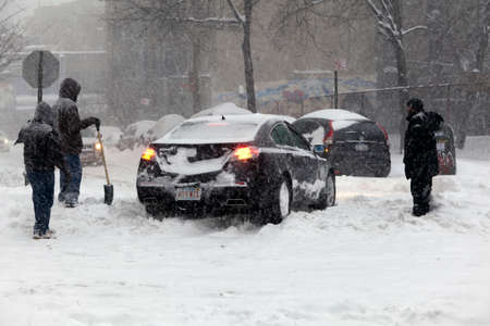 bronx county: BRONX, NEW YORK - JANUARY 23: People help an auto that is stuck in snow during blizzard Jonas.  Taken January 23, 2016, in the Bronx,  New York.