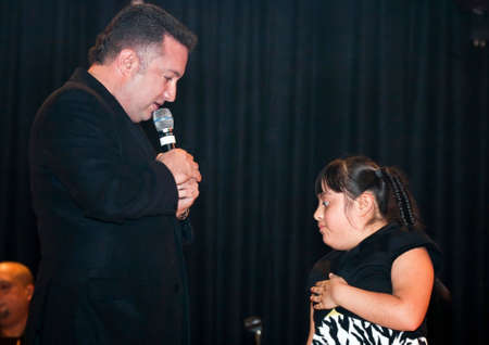 march 17: BRONX, NEW YORK - MARCH 17: Samuel Hernandez performs with a down syndrome child during a Christian concert for Realizing Possibilities ministry.  Taken March 17, 2012, in  New York.