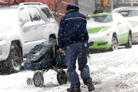 mail man: BRONX, NEW YORK -JANUARY 7:  Mail man pushes mail carriage during snow storm.  Taken January 7, 2017 in New York.