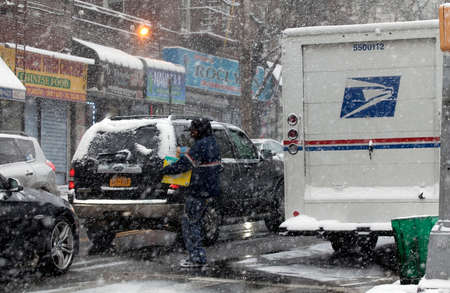 usps: BRONX, NEW YORK -JANUARY 7:  Mailman carries package for delivery during snow storm.  Taken January 7, 2017 in New York.