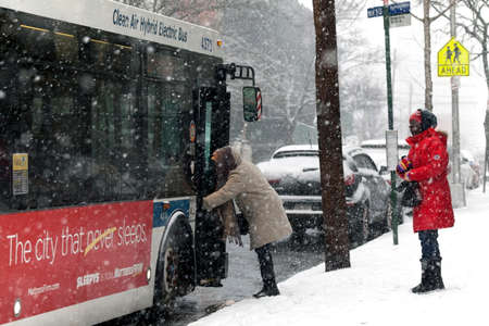 bronx county: BRONX, NEW YORK -JANUARY 7: Woman boarding bus during snow storm.  Taken January 7, 2017 in New York.