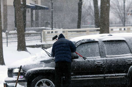 bronx county: BRONX, NEW YORK - MARCH 14:  Man cleans car with brush during snow storm.  Taken March 14, 2017 in New York.