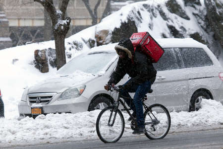bronx county: BRONX, NEW YORK - MARCH 14:  Man makes delivery on bike in snow storm.  Taken March 14, 2017 in New York.