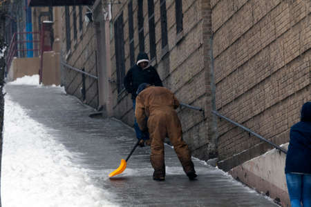 bronx county: BRONX, NEW YORK - MARCH 14: Man shovels street during snow storm.  Taken March 14, 2017 in New York.