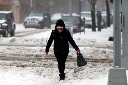 bronx county: BRONX, NEW YORK - MARCH 14: Lady walking along street in snow storm.  Taken March 14, 2017 in New York.