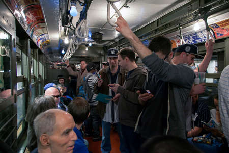 bronx county: BRONX, NEW YORK, USA - APRIL 10: Yankee fans ride a vintage Low Voltage train to Yankee Stadium for opening day game.  Taken April 10, 2017 in New York. Editorial