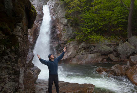 Man Standing in praise in front of Glen Ellis Falls at Pinkham Notch in New Hampshire Фото со стока